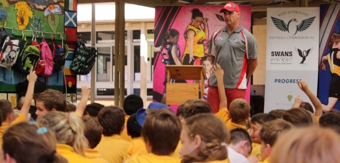 Swans representative gives a speech to kingegarten kids on a mat